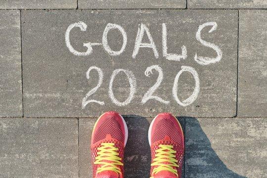 2020 goals, written on gray sidewalk with woman legs in sneakers, top view