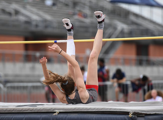 Young girls jumping high for a high jump track meet