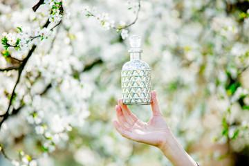 Female hand holding perfume bottle near flowering tree.