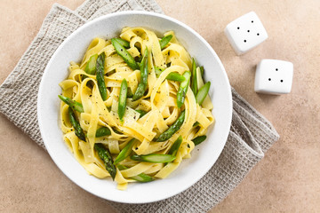 Fresh homemade pasta dish of fettuccine or tagliatelle, green asparagus, garlic and lemon juice in bowl, ground black pepper on the top, salt and pepper shaker on the side, photographed overhead