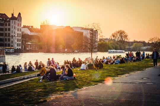 People enjoying sunset at river next to the Berlin Wall / East Side Gallery  in Berlin, Germany