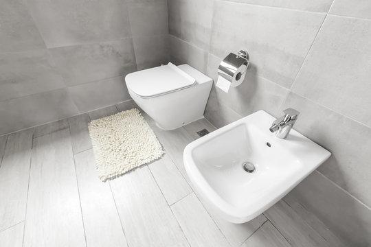 White ceramic bidet and toilet at luxury bathroom interior
