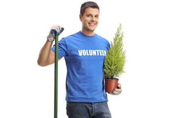 Young male volunteer with a shovel holding a plant