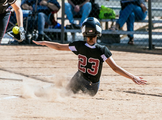 Female teenage softball player in black uniform sliding into home plate before the catcher can make the tag.