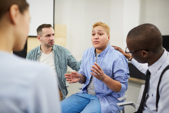 Portrait of mixed raced woman  sharing troubles emotionally during group therapy session, copy space