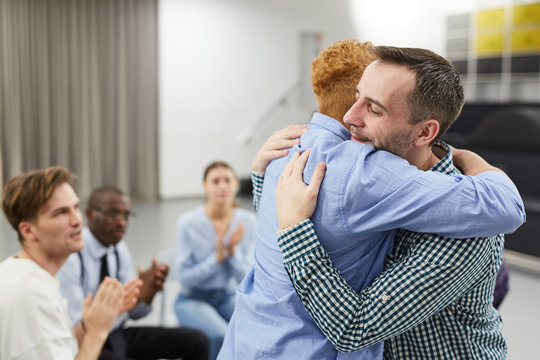 Side view  portrait of mixed race woman hugging psychologist during therapy session in support group, copy space