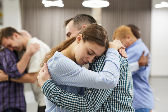 Waist up portrait of people hugging during group therapy session, focus on smiling young woman in foreground