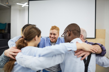 Group of people hugging all together during therapy session in support meeting, copy space Wall mural