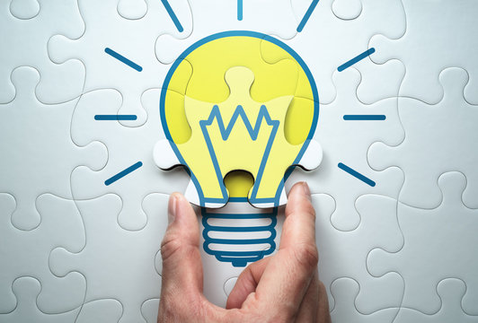 Concept image of solution.  Finding answer to problem.Solving lightbulb jigsaw puzzle.