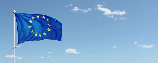 EU flag waving against blue sky with clouds. Copy space
