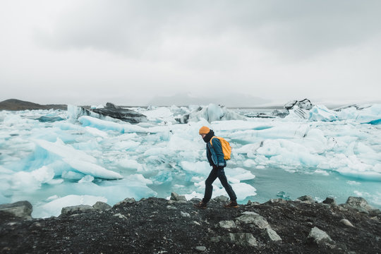 Young girl standing on the sea shore covered in ice floes looking at the Nordic landscape in Iceland