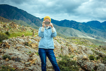 Woman blogger takes off photo and video by smartphone on the background of mountains and cloudy sky. Traveling lifestyle modern technology. Girl tourist taking a photo on a smartphone.