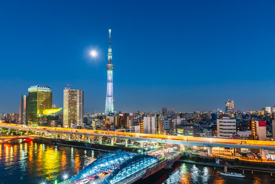 Tokyo Skytree and Sumida river at night with full moon in Asakusa district, Tokyo city, Japan.