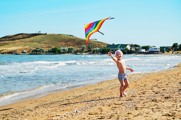 05d9206010 Happy laughing little boy flying a colorful kite in sand on beautiful beach.  Child with