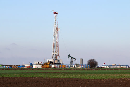 land oil and gas drilling rig and pump jack in oilfield