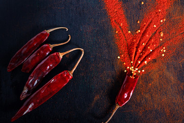 Red Chili pepper flakes and chili powder burst on black background