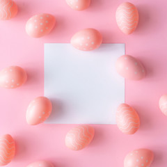 Pink Easter eggs on pink table with white paper card note. Minimal Easter background composition. Flat lay.