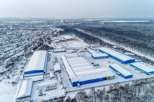 Large warehouse complex, several buildings covered with snow. Winter cityscape.