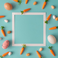 Easter pattern made with carrots and eggs on bright blue background. Creative minimal holiday concept. Flat lay.
