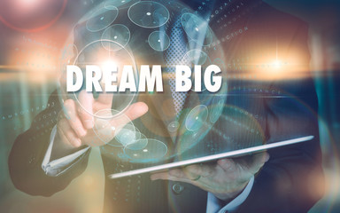 A hand selecting a Dream Big business concept on a futuristic computer display.