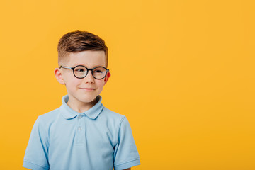 handsome little boy in glasses, dressed in blue shirt, isolated on yellow background, copy space