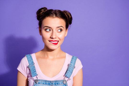 Close up photo beautiful amazing she her lady two buns red pomade bite upper lip tricky mood look side empty space wear casual t-shirt jeans denim overalls clothes isolated purple violet background
