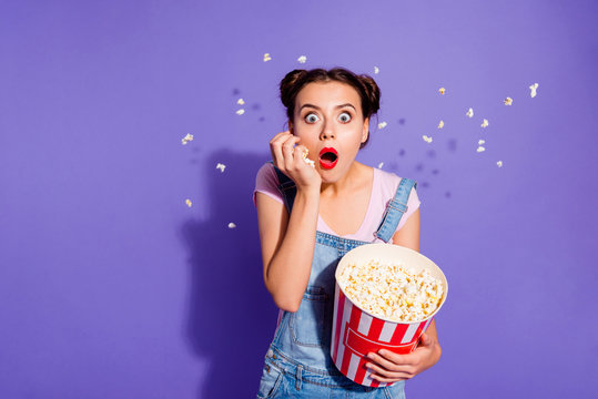 Close up photo beautiful she her lady buns watch tv show popcorn flying everywhere eyes full fear mouth eyes open wear casual t-shirt jeans denim overalls clothes isolated purple violet background