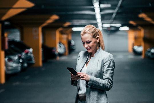 Blonde elegant woman using smartphone in parking garage.