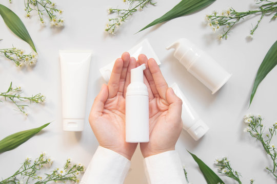 Beauty natural skincare products development concept. Dermatologist hands​ holding blank cosmetic skincare bottle w/ pump dispenser and​ organic ingredient on​ white​ background. ​Top​ view. Close up.