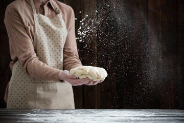 hands cooking dough on dark wooden background