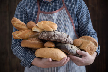 hand and different types of bread on wooden background