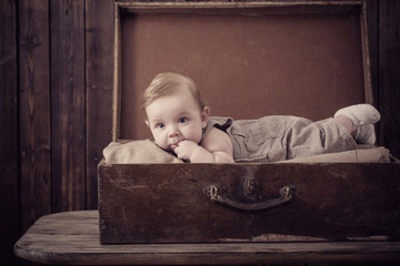 little baby in suitcase on wooden background