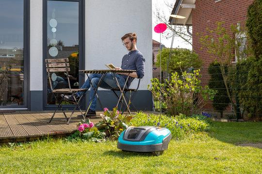Roboterrasenmäher im Hintergrund Mann mit Buch