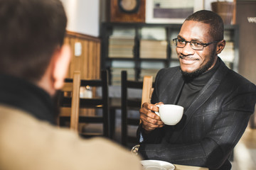 Multicultural african and caucasian businessmen negotiate in a cafe. Wall mural