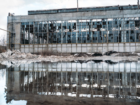 Flooded  territory of abandoned ruined industrial factory building with broken facade and windows, reflection in water