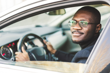 A young businessman in a suit sits at the wheel of a expensive car. Fototapete