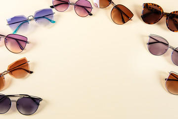 Different sunglasses on yellow background. Frame. Summer banner. Copy space.