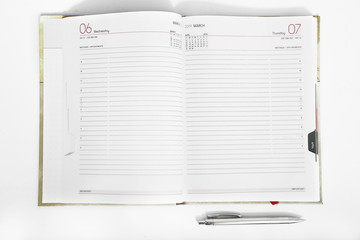 Portrait of open diary with pen. Isolated on the white background.