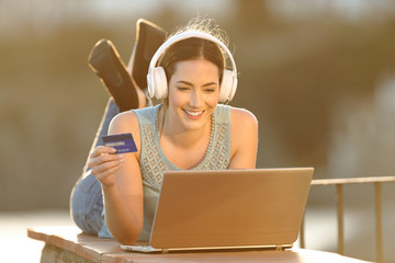 Happy woman uses a laptop to buy online music or media