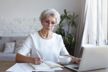 Picture of serious stylish mature businesswoman in eyeglasses sitting at wooden desk, making notes in copybook, using laptop computer, searching information online on internet, having focused look