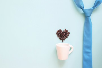 Happy Father's Day concept with blue colour necktie and coffee cup with coffee beans heart shape on pastel background