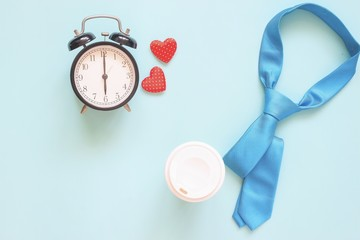 Blue colour necktie, coffee cup and clock on pastel background. Top view, Father's Day concept