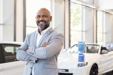Happy salesman in car showroom