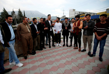 Biwar Abdullah, 25, an Iraqi Kurdish local footballer, who looks like the football player Cristiano Ronaldo, takes pictures with people in the district of Soran, northeast of Erbil