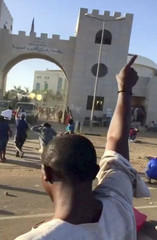 Still image taken from video showing protester raising his arm during a rally outside the defence ministry in Khartoum