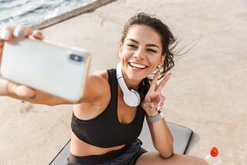 Smiling sportswoman taking selfie