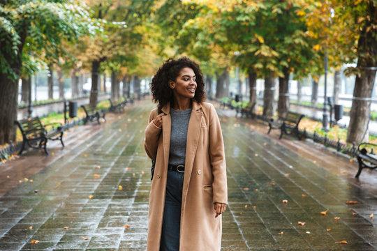 Beautiful young african woman wearing coat walking outdoors