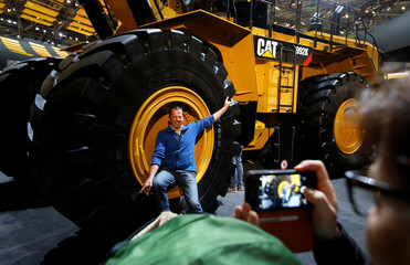 A man poses in a wheel of a Caterpillar excavator at the 'Bauma' Trade Fair in Munich