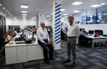 The president and the executive director of Wilobank, Guillermo Francos and Juan Carlos Ozcoidi, pose for a picture in the offices of Wilobank, in Buenos Aires