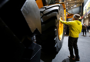 A man watches a wheel of a Caterpillar excavator at the 'Bauma' Trade Fair in Munich